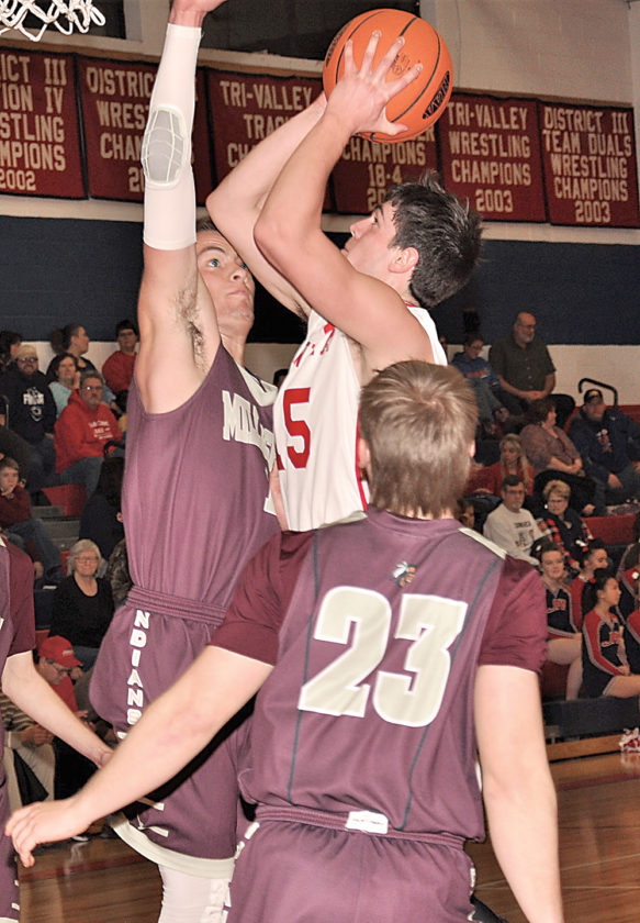 Sentinel photo by BROOKEFOSTER  Juniata's Tyler Clark, center, shoots for two as Millersburg's Matt Snyder, left, and Cole Shomper (23) try to block the shot Wednesday evening in Mifflintown.