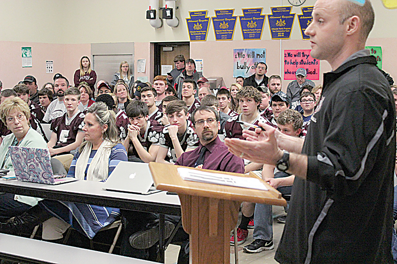 Sentinel photos by JULIANNE CAHILL  East Juniata High School Assistant Football Coach Simon Cameron speaks in favor of the continuation of the co-op program at a school board meeting held Thursday evening at Fermanagh-Mifflintown Elementary School, as members of the team look on.