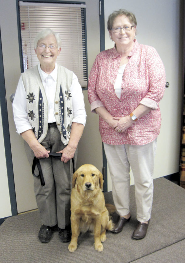 Sentinel photo by JOE CANNON  Jean Swartz, left, leader of the Juniata County Seeing Eye Puppy Club, was recently honored with the 2016 Pennsylvania Community Service Award from the state 4-H program. She was nominated by Teresa Ellinger, right, 4-H program assistant, and accompanied to Tuesday's meeting of the Juniata County Commissioners by Cameo, who is in training to become a seeing eye dog.