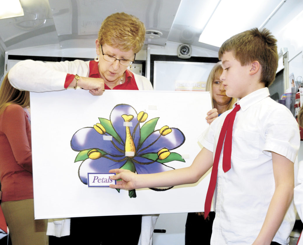 "Sentinel photos by BUFFIE BOYER Instructor Tina Goss, left, asks Sacred Heart School second grade student Sawyer Myers to place the petal sign on the board as the class learns the parts of a flower during the ""Bee-utiful"" lesson Thursday in the Mobile Ag Ed Science Lab."