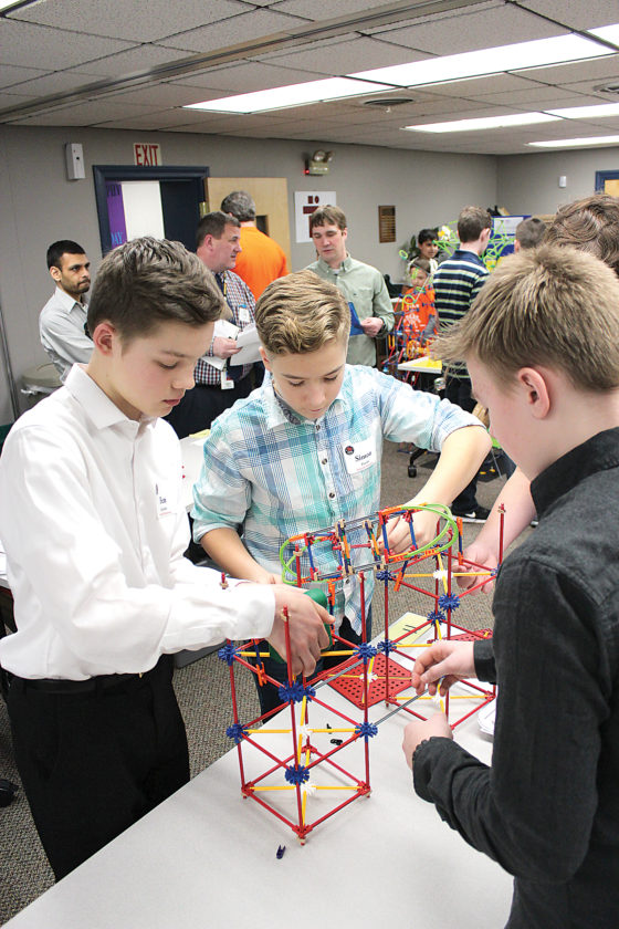 Sentinel photo by JULIANNE CAHILL  Belleville Mennonite School students, from left, Ben Hartzler, Simon Peachey and Gabriel Amspacker use K'nex building pieces to assemble an eco-friendly amusement park ride they designed during the 2017 K'nex STEM Design  Challenge, held Friday at Tuscarora Intermediate Unit 11 in McVeytown. Not pictured is teammate Zachary Snook.