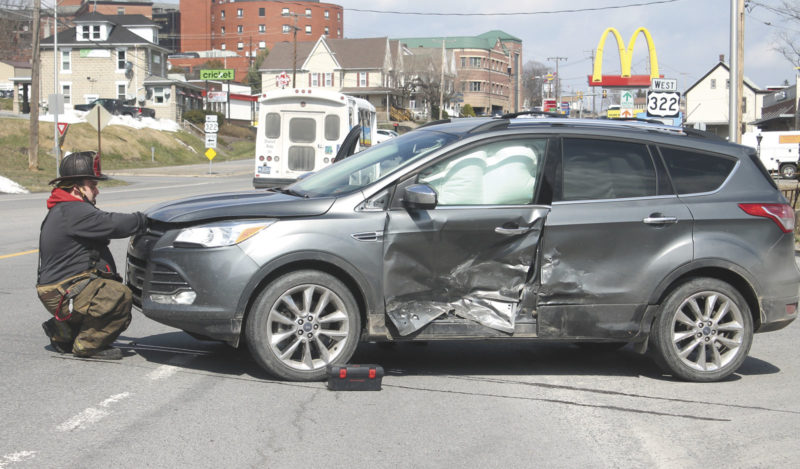 Sentinel photos by LAUREN KERSHNER  A firefighter from the City Hook and Ladder tries to pop the hood of a Ford Escape after the vehicle was  involved in an accident Tuesday at the Electric Avenue and Mill Road interchange, Derry Township.