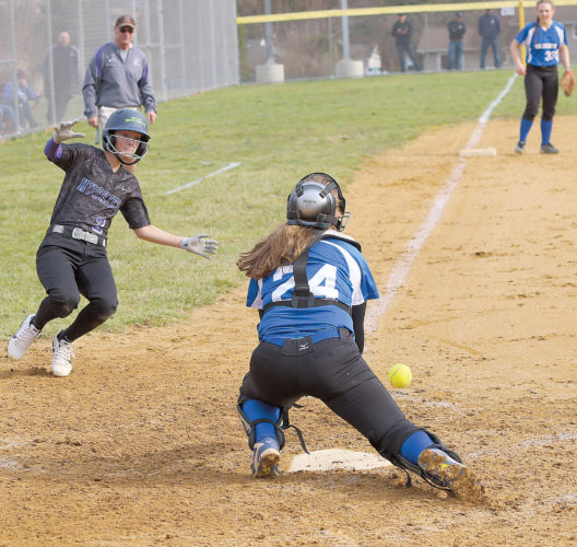 Sentinel photo by MATT STRICKER Mifflin County's Maxie Johnson, left, begins her slide into home as Central Mountain catcher Autumn Young looks to handle the relay throw from the outfield Friday in Lewistown.