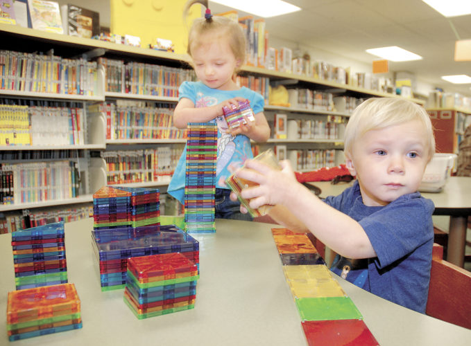 Sentinel photo by BUFFIE BOYER Twins Lucy and Lincoln Rheel, 2, children of Dustin and Danielle Rheel, of Belleville, play with magnetic tiles in the 'play to learn' area of the Mifflin County Library.