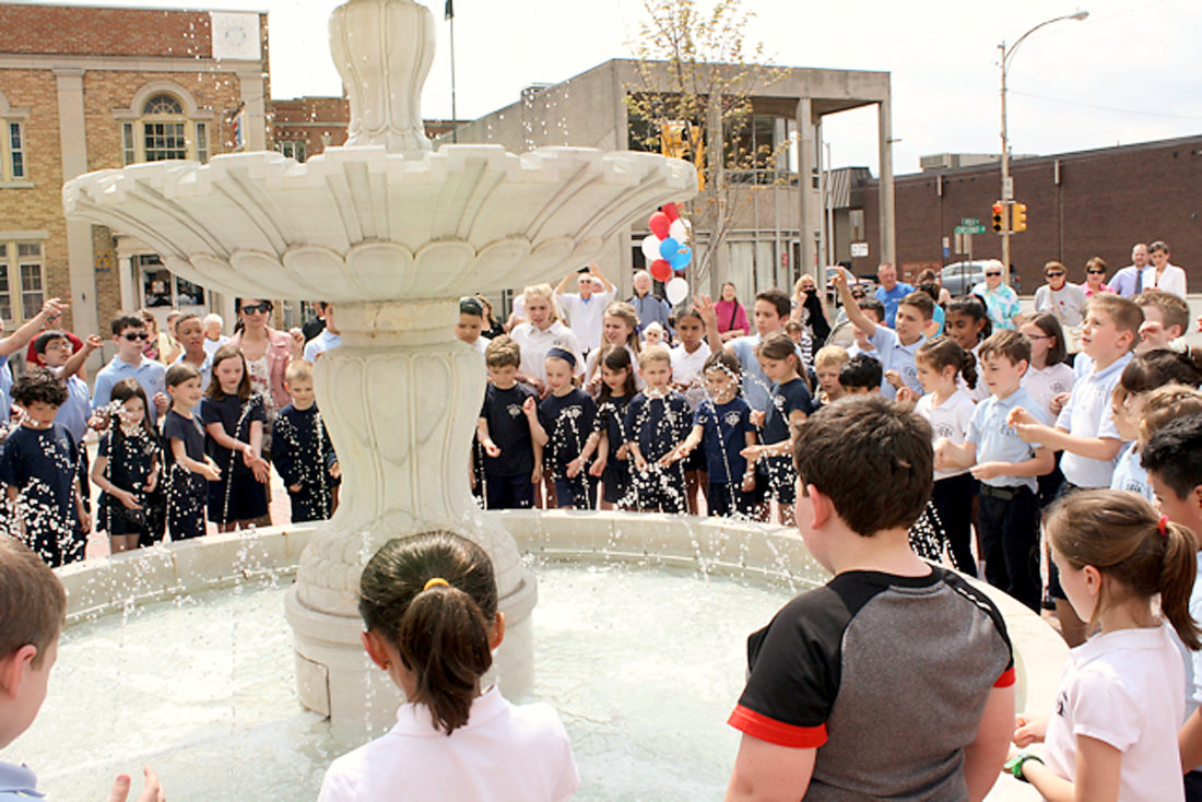 Sentinel photo by KRISTEN PRICE Students from Sacred Heart of Jesus School toss coins into the fountain at Fountain Square Park  Friday during a celebration presented by the Juniata River Valley Chamber of Commerce and Visitors Bureau, Lewistown Borough and Downtown Lewistown Inc. Students from Sacred Heart School make wishes as they toss coins in the now operating fountain.