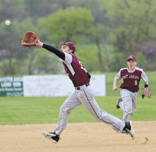 Sentinel photo by MATT STRICKER East Juniata first baseman Seth Rowe, left, stretches for a catch on a hit to the infield with backup from second baseman Ethan Jamison (8) Monday in Cocolamus.