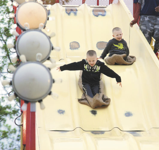 Sentinel photo by BRADLEY KREITZER  Tad Wilson, 5, left, and his brother Tate Wilson, 3, of McClure, glide down the slide during the 21st  annual Embassy Fair Monday evening at Kish Park.