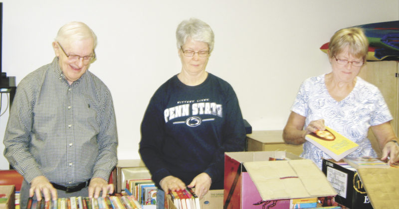 Submitted photo  Mifflin County retired school employees, from left, Leonard Ronk, Dottie Peiffer and Gloria Richards get ready for Mifflin County Library's spring book sale, which begins today and continues through Sunday. The sale is held in the community room of the  library at 123 N. Wayne St., Lewistown. Hours for the sale are  9 a.m.-8 p.m. today;  9 a.m.-4 p.m.  Thursday, Friday and Saturday; and 1:30-3:30 p.m. Sunday.