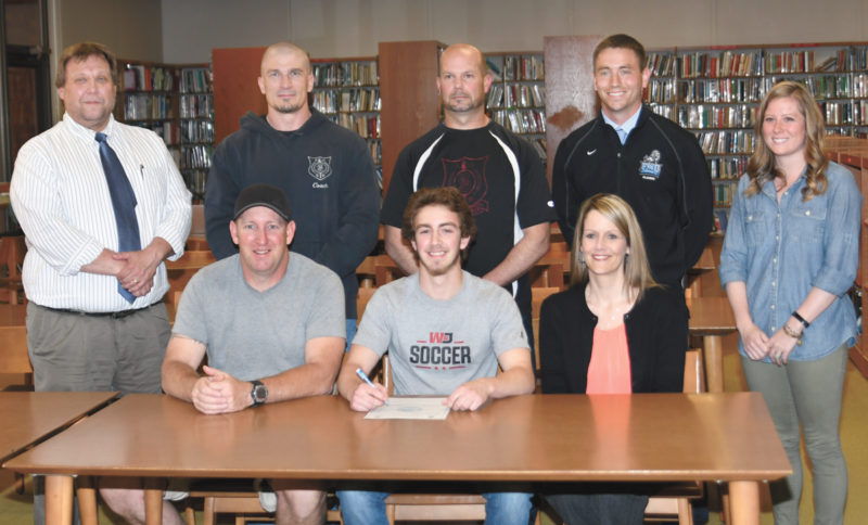 Sentinel photo by JEFF FISHBEIN  Juniata senior Chase Goodwin, center, flanked by parents Rich and Heidi, is headed to Washington and Jefferson to play soccer. With him at Wednesday's recognition ceremony are, from left, principal Ed Apple, former Juniata coach Clint Brackbill, coach Nevin Burns, incoming coach Jared Byler and athletic director Alyssa Adam.