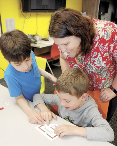 Sentinel photo by BUFFIE BOYER  Lori McMonigal, right, watches her son Ethan, bottom, and Jonas Harpster, make a simple paper circuit into a name tag Thursday while visiting the Tuscarora  Intermediate Unit 11 in McVeytown. Staff members from PA CareerLink Mifflin County participated in 'Take Your Child to Work Day' and took their kids to the TIU to do some STEM activities. The children were playing with a purpose as they learned about  circuits, robots and code using Ozobots.