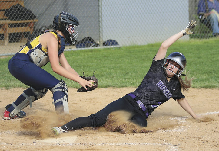 Sentinel photo by MATT STRICKER  Mifflin County's Eleana Eckley slides into home under the tag of Cedar Cliff catcher Olivia Wagner scoring the first run in the Huskies' three-run fourth inning Thursday in Lewistown.