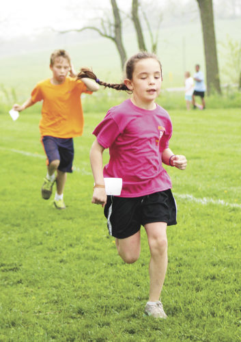 Sentinel photo by TABITHA GOODLING  Second grade student Julia Fuller makes her way through the Race for Education, ahead of classmate Jacob Sellers. Juniata Mennonite School held the annual race Thursday at the school.