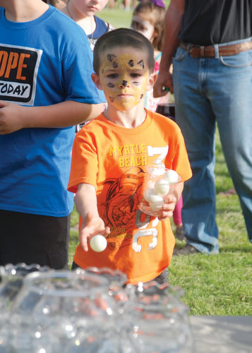 Sentinel photo by BRADLEY KREITZER Chase Yetter, 5, of Burnham, tosses a ping pong ball at the goldfish game during the Indian Valley Elementary School Spring Fest Friday evening in Reedsville.