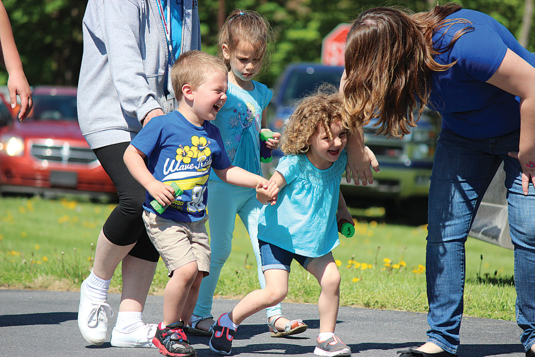 Sentinel photo by JULIANNE CAHILL Brycen Wagner, left, and Rylee Pully, from Lewistown Children's Center, giggle as they run to catch up during a parade Friday morning in Lewistown. Classmate Leanna Siracusa is pictured walking behind them. Students and staff from the center walked across the street to Ohesson Manor where they played handmade instruments for the residents. The parade was part of the Week of the Young Child, a celebratory time set aside each April for special events. The week is sponsored by the National Association for the Education of Young Children. Families of students are invited to the center each year on Friday for the annual music parade and picnic lunch.