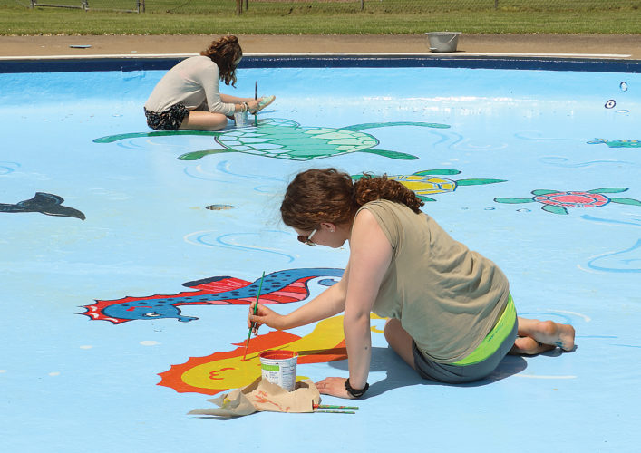 Sentinel photo by MATT STRICKER Mifflin County High School art class seniors Allie Amspacker, back left, and McKenna Stauffer paint aquatic characters on the bottom of the Burnham Community baby pool Friday in preparation for the pool's opening day in May.