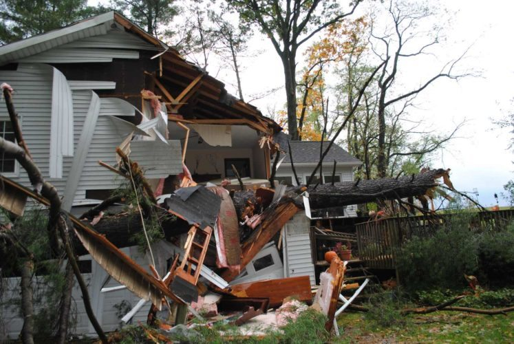A huge evergreen smashed into Frank and Kathy Dwyer's house along Noll Lane south of Mill  Hall last night, causing significant damage and propelling Frank out of the home. He later died. (Photo by Lana Muthler/The Express).