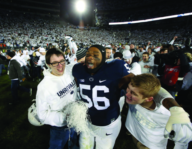 Penn State's Tyrell Chavis (56) celebrates with fans as they rush the field after Penn State upset Ohio State 24-21 in an NCAA college football game in State College, Pa., Saturday, Oct. 22, 2016. (AP Photo/Chris Knight)