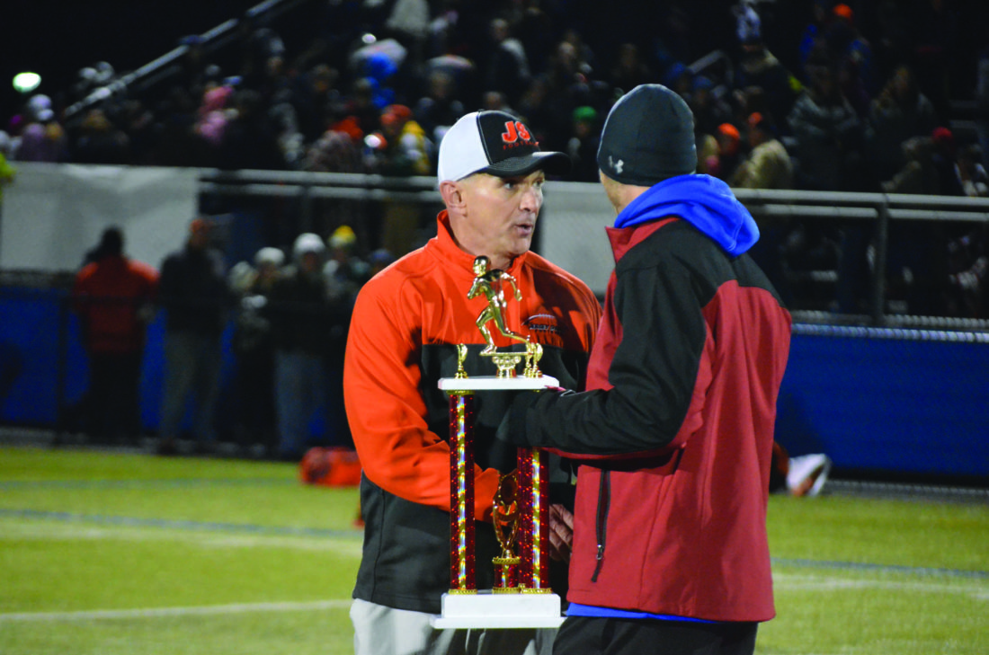 Jersey Shore head coach Tom Gravish receives a trophy from CM athletic director George Bidwell, on Friday night.