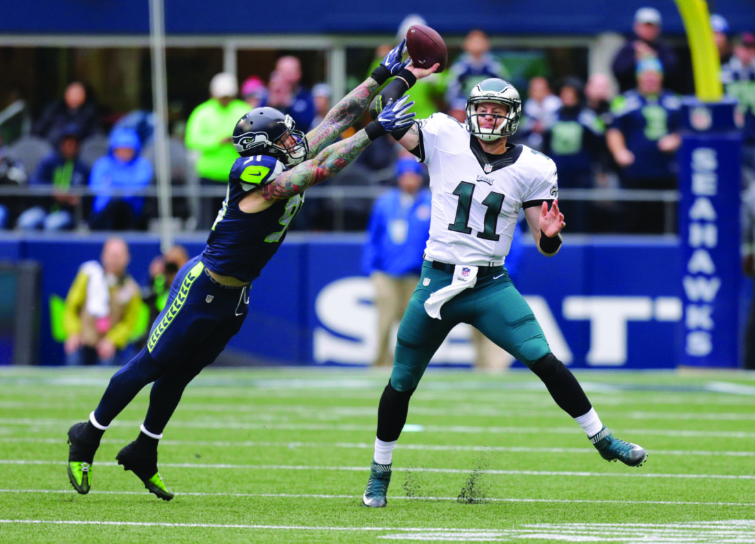 Seattle Seahawks outside linebacker Cassius Marsh, left, hits the arm of Philadelphia Eagles quarterback Carson Wentz (11) causing an incomplete pass in the first half of an NFL football game, Sunday, Nov. 20, 2016, in Seattle. (AP Photo/Stephen Brashear)