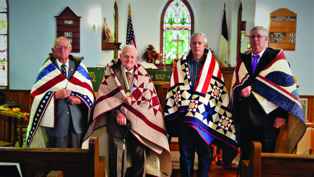 Pictured from left are brothers Air Force Lt. Col. Ken Royer and Army Airman 2nd Class Carl Royer; Ken's son, Air Force Maj. Dennis Royer; and Carl's son, Staff Sgt. Shane Royer, wearing their Quilts of Valor.  AMBER MORRIS/ FOR THE EXPRESS