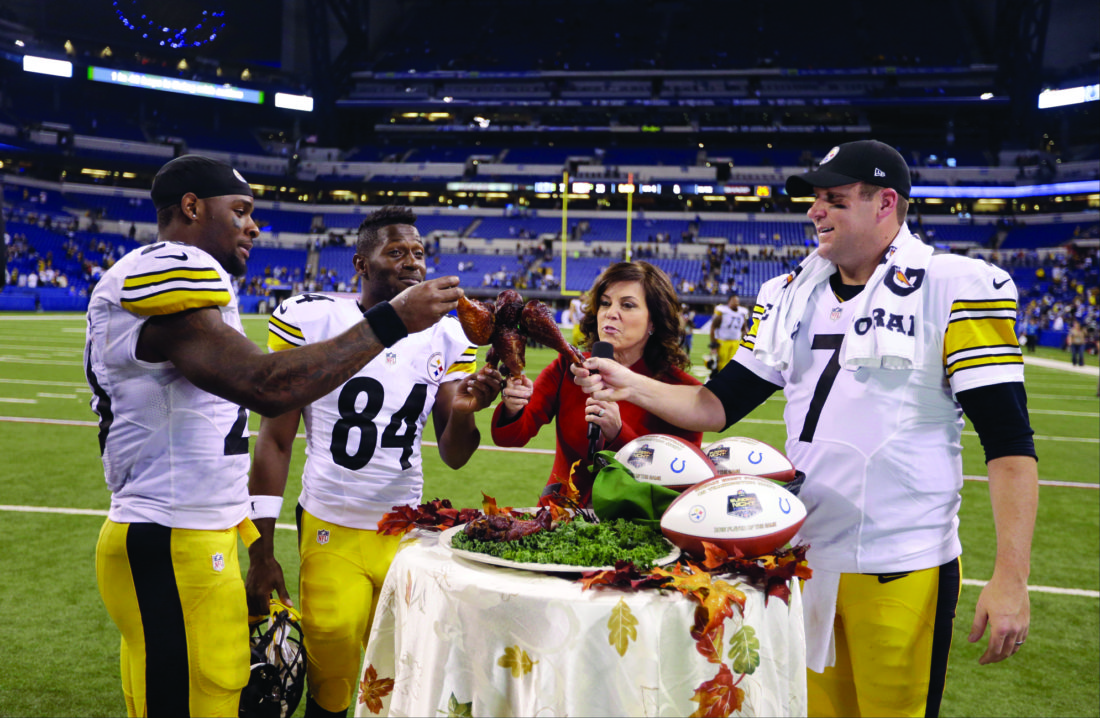 Pittsburgh Steelers running back Le'Veon Bell, left, and wide receiver Antonio Brown (84) prepare to eat turkey legs with teammate quarterback Ben Roethlisberger, right, as Michele Tafoya of NBC sports watches following an NFL football game between the Indianapolis Colts and the Pittsburgh Steelers Thursday, Nov. 24, 2016, in Indianapolis. Pittsburgh won the game 28-7. (AP Photo/Michael Conroy)