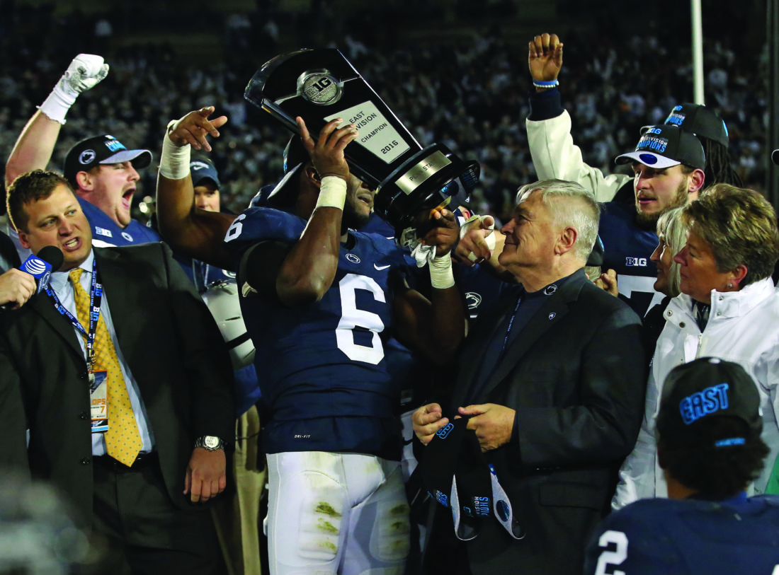 Penn State's Malik Golden (6) hoists the Big Ten East division trophy after defeating Michigan State 45-12 in an NCAA college football game in State College, Pa., Saturday Nov. 26, 2016. (AP Photo/Chris Knight)