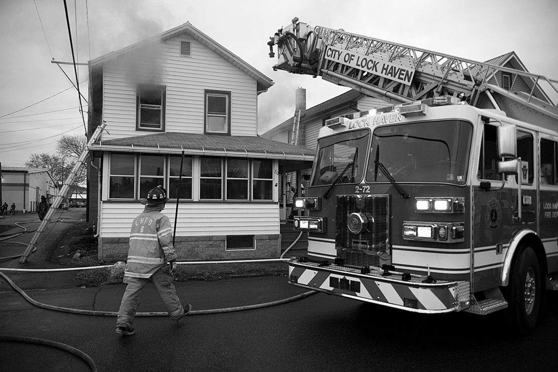 SPENCER McCOY/THEEXPRESS Firefighters work at the scene of a blaze on Commerce Street in Lock Haven yesterday.