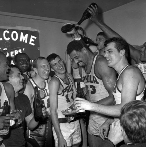 FILE - In this April 12, 1967, file photo, Wilt Chamberlain of the Philadelphia 76ers gets champagne poured on him in the 76ers dressing room after Philadelphia defeated the Boston Celtics 140-116 to win the Eastern Division final. Surrounding Chamberlain are, from left, Bob Weiss, Matt Guokas (14), center left, Chamberlain, Wally Jones (drinking from a bottle) and Dave Gambee, right.  The 1966-67, 76ers _ led by Chamberlain, Hal Greer and Billy Cunningham _ were once hailed as the greatest NBA team of all time. But as the years moved on, their place in NBA history has receded. The team will be honored at Saturday night's game.(AP Photo/File)