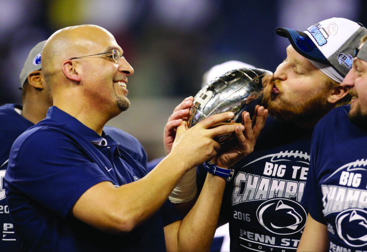 Penn State's Derek Dowrey, right, kisses the trophy held by head coach James Franklin after Penn State defeated Wisconsin in the Big Ten championship NCAA college football game Sunday, Dec. 4, 2016, in Indianapolis. Penn State won 38-31. (AP Photo/AJ Mast)