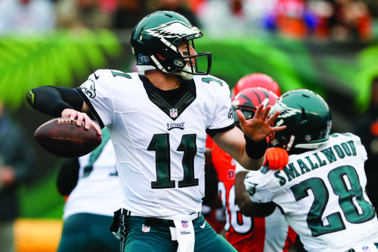 FILE - In this Sunday, Dec. 4, 2016 file photo, Philadelphia Eagles quarterback Carson Wentz passes in the first half of an NFL football game against the Cincinnati Bengals in Cincinnati. That 3-0 start for Carson Wentz and Philadelphia is a distant memory at this point. The Eagles have lost three straight games by a double-digit margin and seven of nine. (AP Photo/Gary Landers, File)