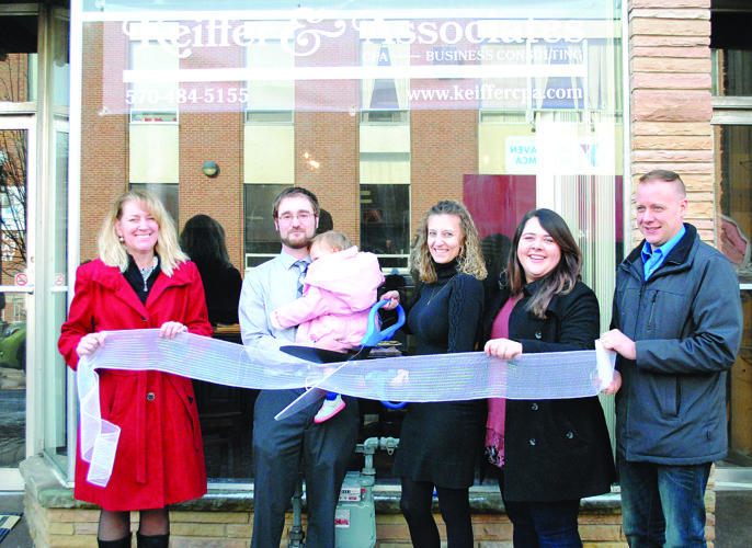 WENDY STIVER/THE EXPRESS Amanda R. Keiffer, CPA, cuts the ribbon Wednesday morning in front of her new business, Keiffer & Associates LLC, at 142 W. Water St., Lock Haven. From left are April Henry-Bittner of the Clinton County Economic Partnership; the new business owner's husband, Tom Keiffer, holding their daughter, Morgan; Amanda Keiffer with the ceremonial scissors; Downtown Manager Natasha Gorham; and Jeff Miller, president of the Downtown Lock Haven Inc. Board of Directors.