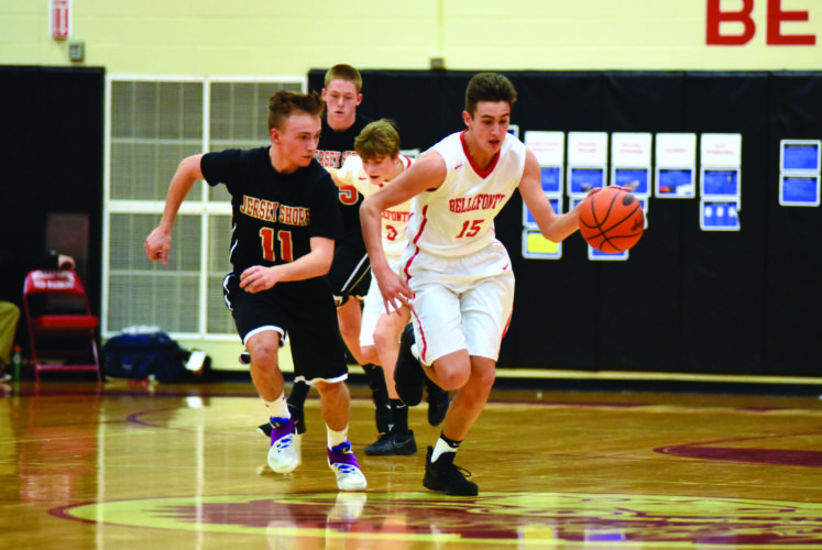 Ben McCartney (15) of Bellefonte High School runs the ball up the court as Jersey Shore's Mac Griswold (11) chases after him to play defense. The Bulldogs defeated the Red Raiders, 54-53. (The Express/Tim Weight)