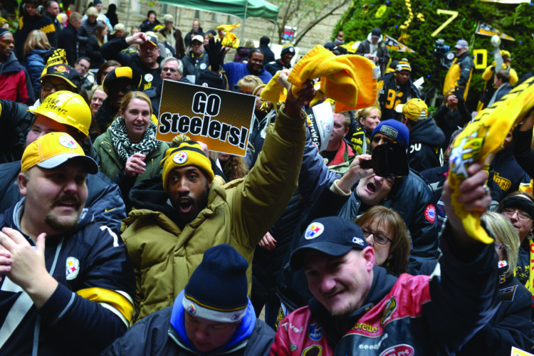 """Jeral Wolford, from Mckeesport, Pa. waves a """"terrible towel"""" and cheers amid the crowd at a rally for the Pittsburgh Steelers in the courtyard of the Allegheny County Courthouse on Friday, Jan/ 13, 2017, in Pittsburgh. The Steelers play the Kansas City Chiefs in Kansas City on Sunday night in the NFL football playoffs. (Pam Panchak/Pittsburgh Post-Gazette via AP)"""