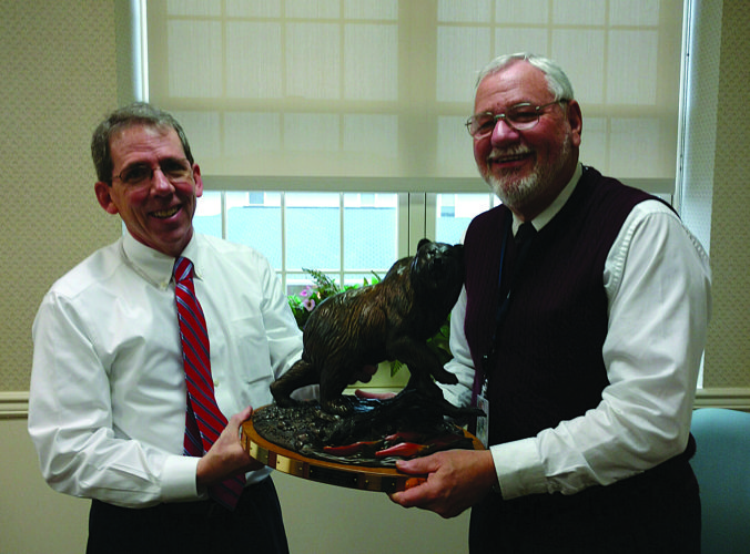 "PHOTO PROVIDED Lycoming County Commissioner Chair R. Jack McKernan, left, hands over the Bear Trophy to Clinton County Commissioner Chair Robert ""Pete"" Smeltz."