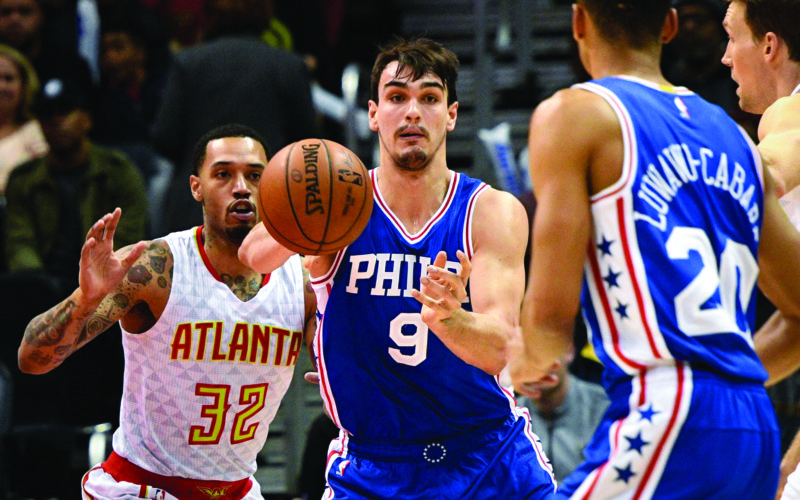 Philadelphia 76ers forward Dario Saric (9), of Croatia, passes to Philadelphia 76ers guard Timothe Luwawu-Cabarrot (20), of France, as Atlanta Hawks forward Mike Scott (32), and guard Mike Dunleavy, right, defends during an NBA basketball game, Saturday, Jan. 21, 2017, in Atlanta. (AP Photo/John Amis)