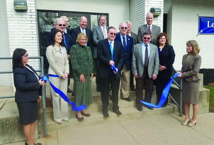 BEN GREEN/THE EXPRESS Muncy Bank President and CEO Rob Glunk cuts the blue ribbon yesterday, officially opening the newest Muncy Bank and Trust Company bank on Central Avenue in Avis. Bank officials and employees are pictured during the ceremony.