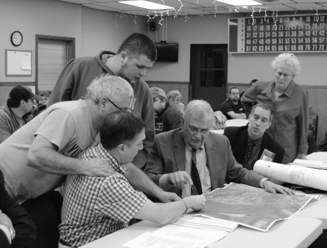 WENDY STIVER/THE EXPRESS Dr. Robert C. Wise II, seated left, and architect Charles Grieb, seated next to him, show Woodward Township residents an aerial photograph of the site where Wise proposes to build a drug and alcohol rehab facility. The idea received its first approval, from the zoning hearing board, Wednesday in the Dunnstown Fire Hall.