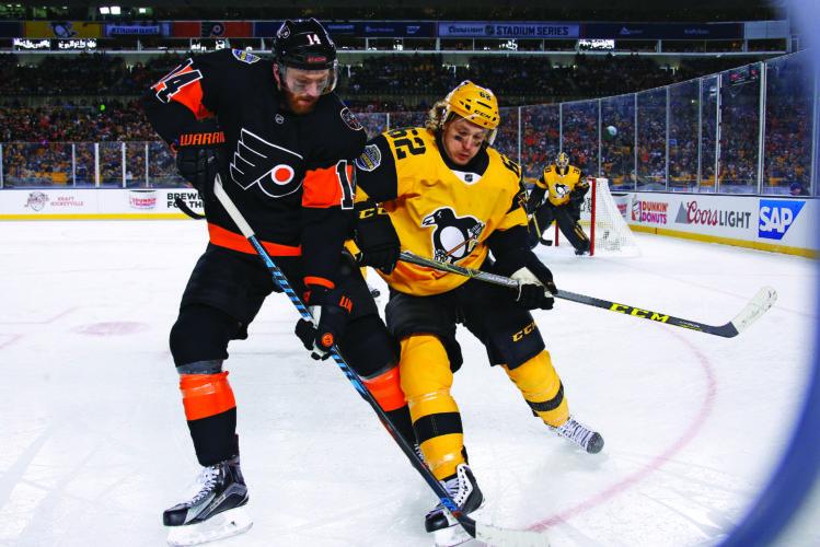 Pittsburgh Penguins' Carl Hagelin (62) battles Philadelphia Flyers' Sean Couturier (14) in the corner during the second period of an NHL Stadium Series hockey game at Heinz Field in Pittsburgh, Saturday, Feb. 25, 2017. (AP Photo/Gene J. Puskar)