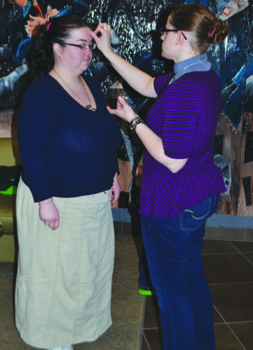 WENDY STIVER/THE EXPRESS Pastor Elizabeth Taylor, right, distributes ashes at Lock Haven University on Ash Wednesday. She is the Protestant Campus Ministry chaplain. Cindi Blazina, campus coordinator for PCM, is seen receiving the ashes.