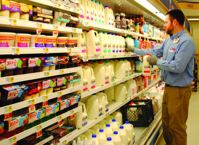 WENDY STIVER/THE EXPRESS Nick Hart, assistant store manager at the Weis Markets grocery store in Lock Haven, kept the milk section stocked Monday afternoon.