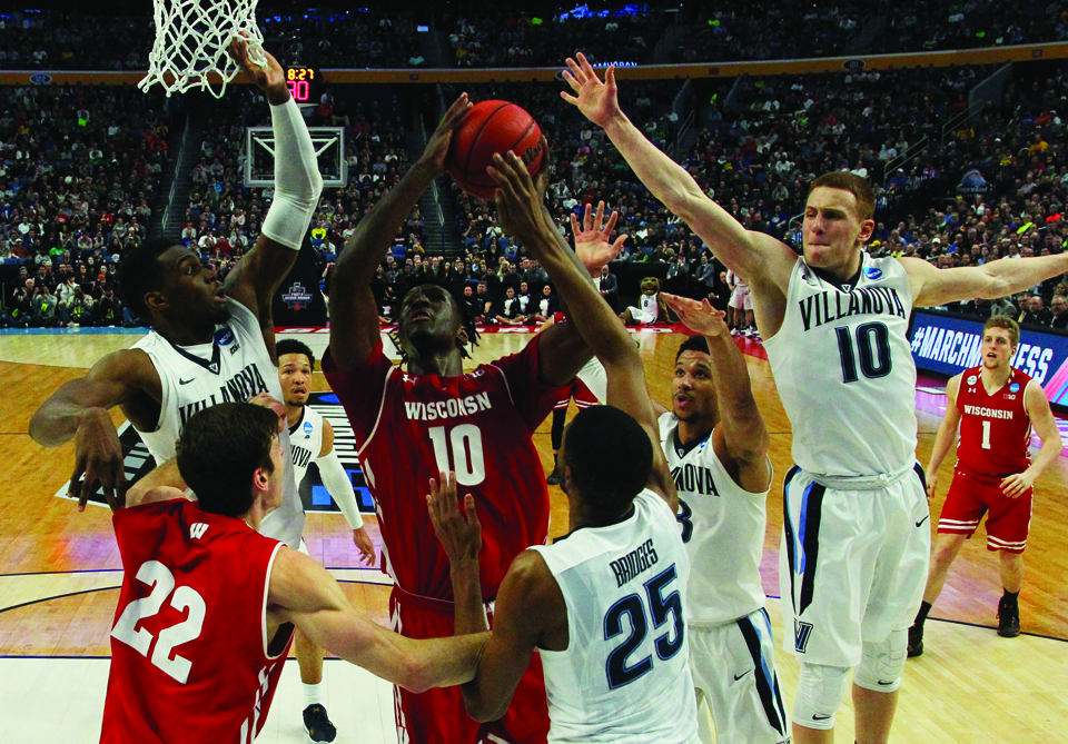 Wisconsin forward Nigel Hayes (10) goes to the basket against Villanova forward Darryl Reynolds, left, guard Donte DiVincenzo (10) and Mikal Bridges (25) during the second half of a second-round men's college basketball game in the NCAA Tournament, Saturday, March 18, 2017, in Buffalo, N.Y.  Wisconsin won, 65-62. (AP Photo/Bill Wippert)