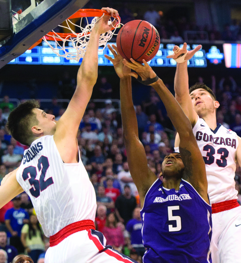 Gonzaga forward Zach Collins (32) sticks his hand through the hoop to block a shot by Northwestern center Dererk Pardon (5) in an NCAA college basketball tournament in Salt Lake City, Saturday, March 18, 2017. (Chris Detrick/The Salt Lake Tribune via AP)