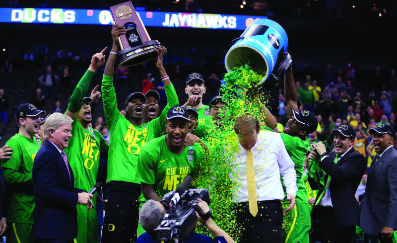 Oregon players celebrate with coach Dana Altman after the Midwest Regional final against Kansas in the NCAA men's college basketball tournament, Saturday, March 25, 2017, in Kansas City, Mo. Oregon won 74-60. (AP Photo/Orlin Wagner)