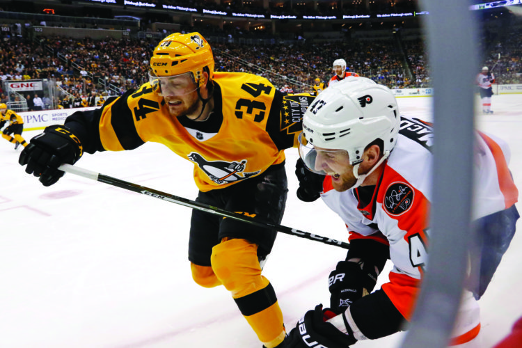 Pittsburgh Penguins' Tom Kuhnhackl (34) chases the puck into the corner with Philadelphia Flyers' Andrew MacDonald (47) defending in the second period of an NHL hockey game in Pittsburgh, Sunday, March 26, 2017. (AP Photo/Gene J. Puskar)