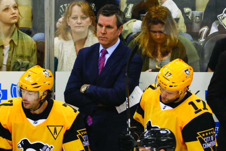 Pittsburgh Penguins head coach Mike Sullivan, center, stands behind his bench during the first period of an NHL hockey game against the Philadelphia Flyers in Pittsburgh, Sunday, March 26, 2017. (AP Photo/Gene J. Puskar)