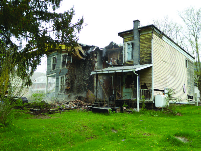 KEVIN RAUCH/THE EXPRESS This long-vacant triplex at 602-606 Ontario Ave., Renovo, at the corner of Sixth Street, was demolished Tuesday by Smith Excavating of Renovo.