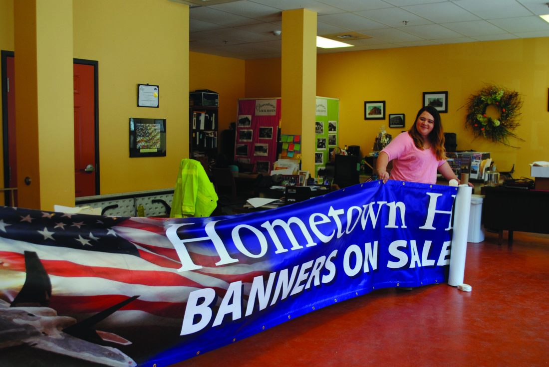 WENDY STIVER/THE EXPRESS Downtown Manager Natasha Gorham unfurls the standard that is now hanging above downtown East Main Street, Lock Haven. It reminds everyone that a new Hometown Heroes Banner Program has started and now is the time to order a banner for the new round.