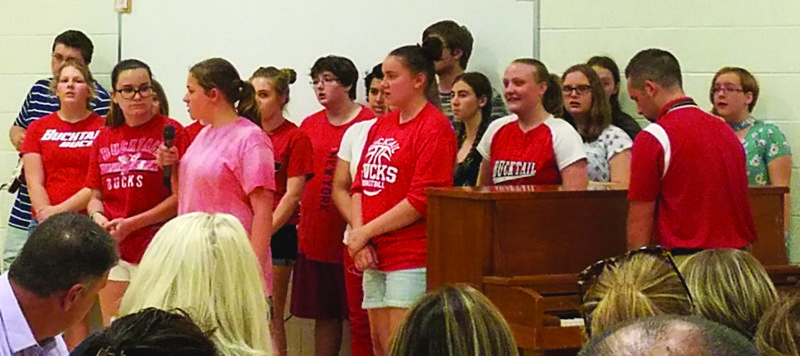 "KEVIN McKEE/THE EXPRESS Bucktail Area High School choir sings in front of the Keystone Central School Board in advance of Thursday night's meeting. The choir, led by music teacher Cole Black, performed Journey's ""Don't Stop Believing"" and received a standing ovation for the rendition."