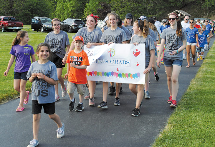 JORDAN SLOBODINSKY/THE EXPRESS The Clinton County Relay for Life opened Friday afternoon and continues today at Riverview Park. The Lock Haven Catholic School Crabs Team includes, Cora Shadal, far left, Harper Coleman in front, and Alex Johnson in the orange shirt, all cancer survivors.