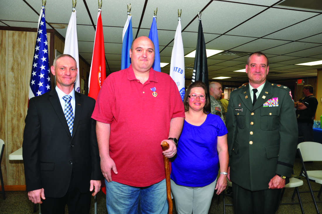 KEVIN RAUCH/THE EXPRESS Twelve years after receiving a traumatic brain injury in Iraq, veteran Brian Getz, second from left, received his Purple Heart in a surprise ceremony. Dozens of fellow veterans, family, friends and even some who had never met Brian packed Renovo Fire Hall. Seen after the ceremony are, from left, Veterans Service Officer of the VFW Benefits Center Sean MacMillen, Brian and his wife Linda, and Lt. Col. (ret.) William Reynolds.